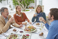 Couples laughing, drinking white wine and eating lunch at patio table - HOXF02670