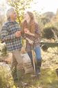 Couple laughing enjoying coffee break gardening sunny autumn garden - HOXF02688
