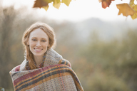 Portrait smiling woman wrapped in blanket in autumn park - HOXF02691