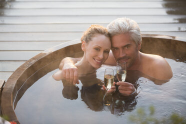 Portrait affectionate couple drinking champagne soaking in hot tub on patio - HOXF02709