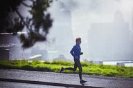 Male runner running on sunny urban sidewalk - HOXF02715