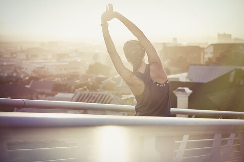 Female runner stretching arms on urban footbridge at sunrise - HOXF02718