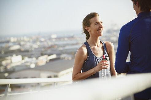 Smiling runner couple resting drinking water on sunny urban footbridge - HOXF02724