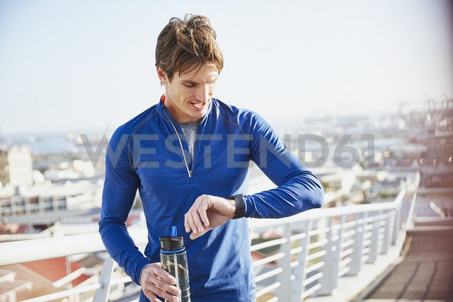 Male runner resting checking smart watch fitness tracker and drinking water on urban footbridge - HOXF02733