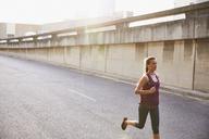 Female runner running on sunny urban street - HOXF02748