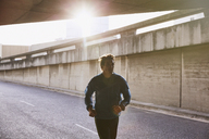 Male runner running into urban tunnel - HOXF02751
