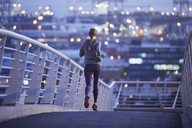 Female runner running on urban footbridge at dawn - HOXF02754
