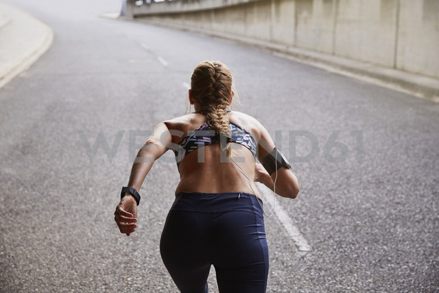 Fit female runner with mp3 player armband running on urban street - HOXF02760