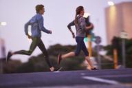 Runner couple running on urban city street - HOXF02763
