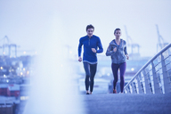 Runner couple running on urban footbridge at dawn - HOXF02769