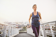 Female runner running on urban footbridge - HOXF02775