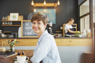Portrait smiling woman drinking coffee at cafe table - HOXF02781