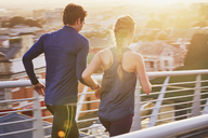 Runner couple running on sunny urban footbridge at sunrise - HOXF02784