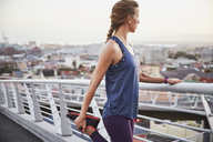Female runner stretching leg on urban footbridge - HOXF02787