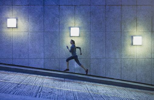 Female runner running ascending illuminated urban ramp - HOXF02790