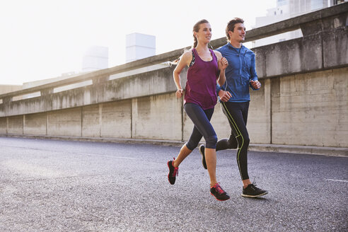 Runner couple running on urban street - HOXF02799