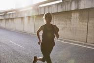 Silhouette female runner running on sunny urban street - HOXF02802