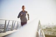 Female runner running on sunny urban footbridge - HOXF02805