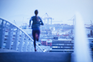 Female runner running on urban footbridge at dawn - HOXF02808