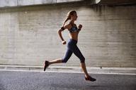 Female runner running on urban street - HOXF02811