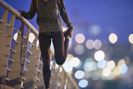 Female runner stretching leg on footbridge at dusk - HOXF02814
