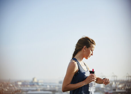 Female runner with water bottle checking smart watch fitness tracker under sunny bleu sky - HOXF02820