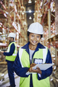 Portrait confident female manager with clipboard in distribution warehouse - HOXF02829