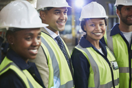 Portrait confident female worker with coworkers in distribution warehouse - HOXF02853