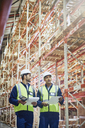 Workers with clipboards and scanner talking in aisle of distribution warehouse - HOXF02865