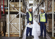 Manager and worker talking in aisle of distribution warehouse - HOXF02868