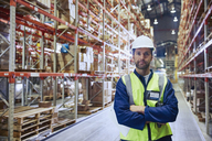 Portrait confident worker with arms crossed in distribution warehouse - HOXF02880