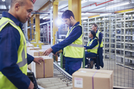 Workers scanning and processing boxes on conveyor belt in distribution warehouse - HOXF02883