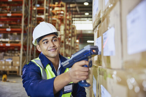 Worker with scanner scanning boxes in distribution warehouse - HOXF02898