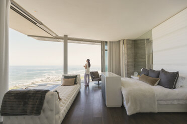 Woman looking at ocean view from modern luxury home showcase bedroom - HOXF02913