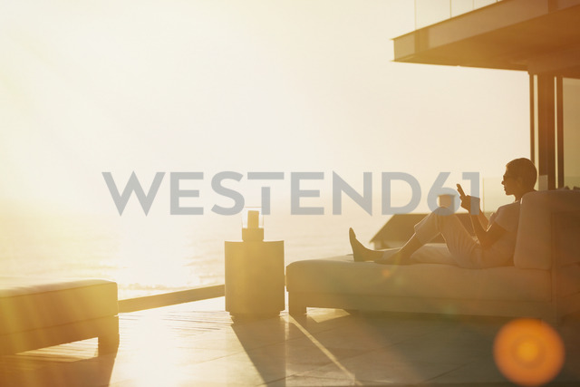 Silhouette woman using cell phone on chaise lounge on luxury balcony with sunset ocean view - HOXF02916