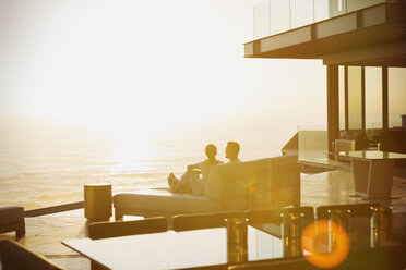 Silhouette couple relaxing on chaise lounge enjoying sunset ocean view - HOXF02919