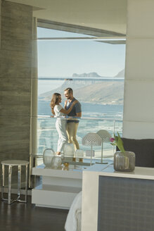 Reflection of couple hugging on luxury balcony with sunny ocean and mountain view - HOXF02925
