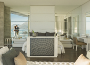Reflection of couple looking at sunny ocean view from modern luxury home showcase bedroom balcony - HOXF02928