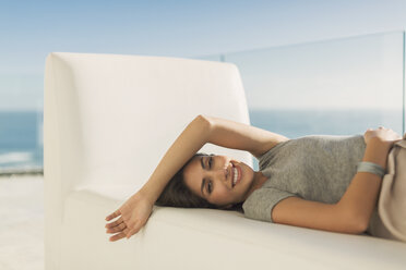Portrait smiling woman relaxing laying on chaise lounge - HOXF02931