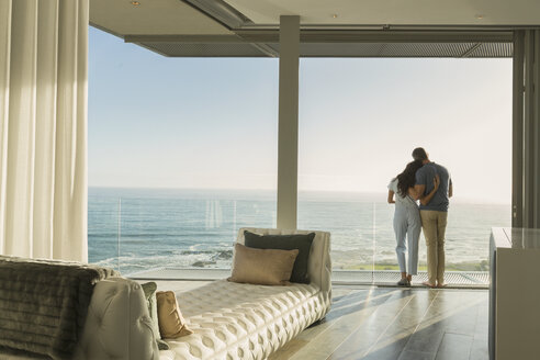 Affectionate couple hugging on sunny luxury balcony with ocean view - HOXF02934