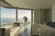 Affectionate couple hugging on modern luxury home showcase bedroom balcony with ocean view - HOXF02937