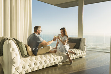 Couple toasting wine glasses on luxury tufted chaise lounge with ocean view - HOXF02940