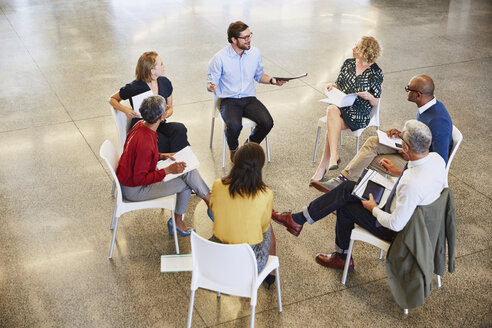 Business people talking in circle meeting - HOXF02973