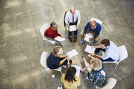 Business people discussing paperwork in meeting circle - HOXF03063