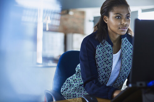 Businesswoman working at laptop in office - HOXF03081