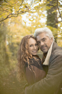 Portrait affectionate couple hugging in autumn woods - HOXF03090