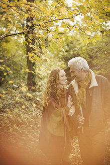 Affectionate couple walking arm in arm in autumn woods - HOXF03096