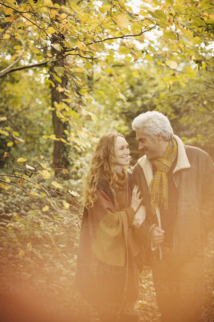 Affectionate couple walking arm in arm in autumn woods - HOXF03096 - Justin Pumfrey/Westend61