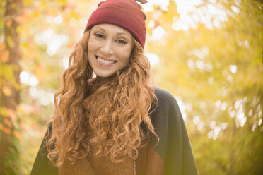 Portrait smiling woman in stocking cap under autumn trees - HOXF03108