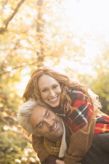 Portrait playful couple piggybacking in autumn woods - HOXF03111
